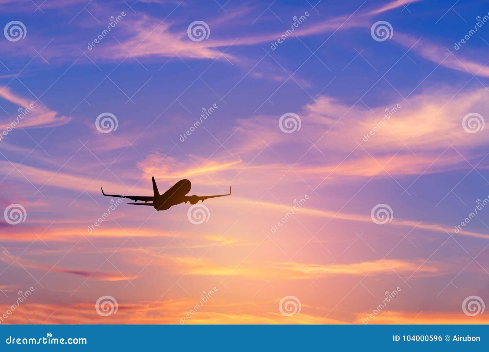 Silhouette самолет пассажира летая прочь внутри к высоченной высоте во время времени захода солнца