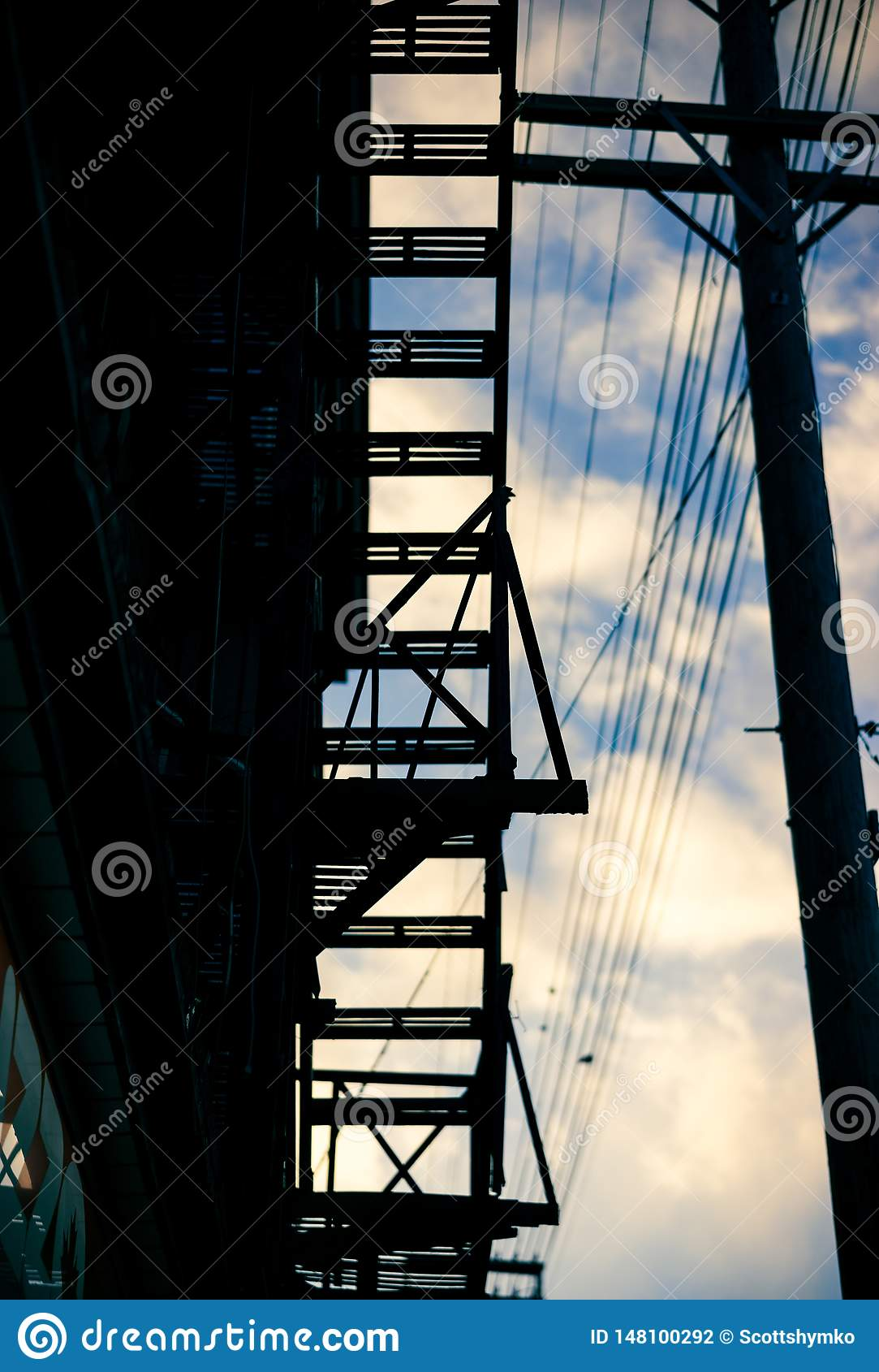 The silhouette of an apartment building`s fire escape