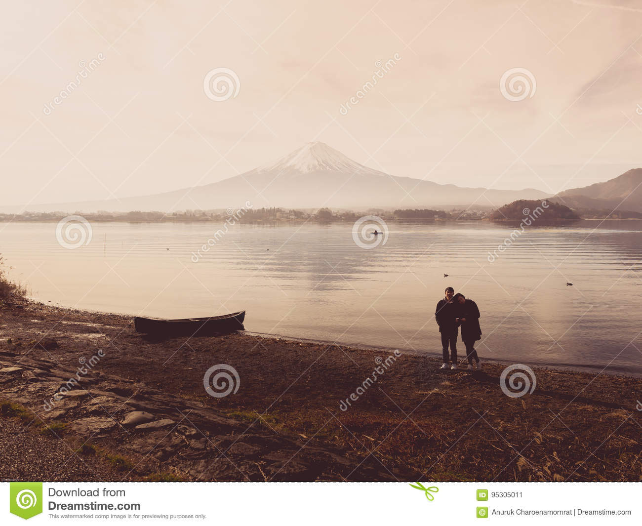 silhouette asia couple traveler 30s to 40s stand and take picture with boat on ground at side of lake kawaguchi on morning time w