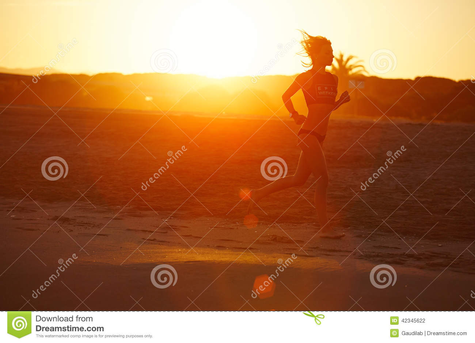 Silhouette of athletic female runner running along the beach an amazing orange sunset on background