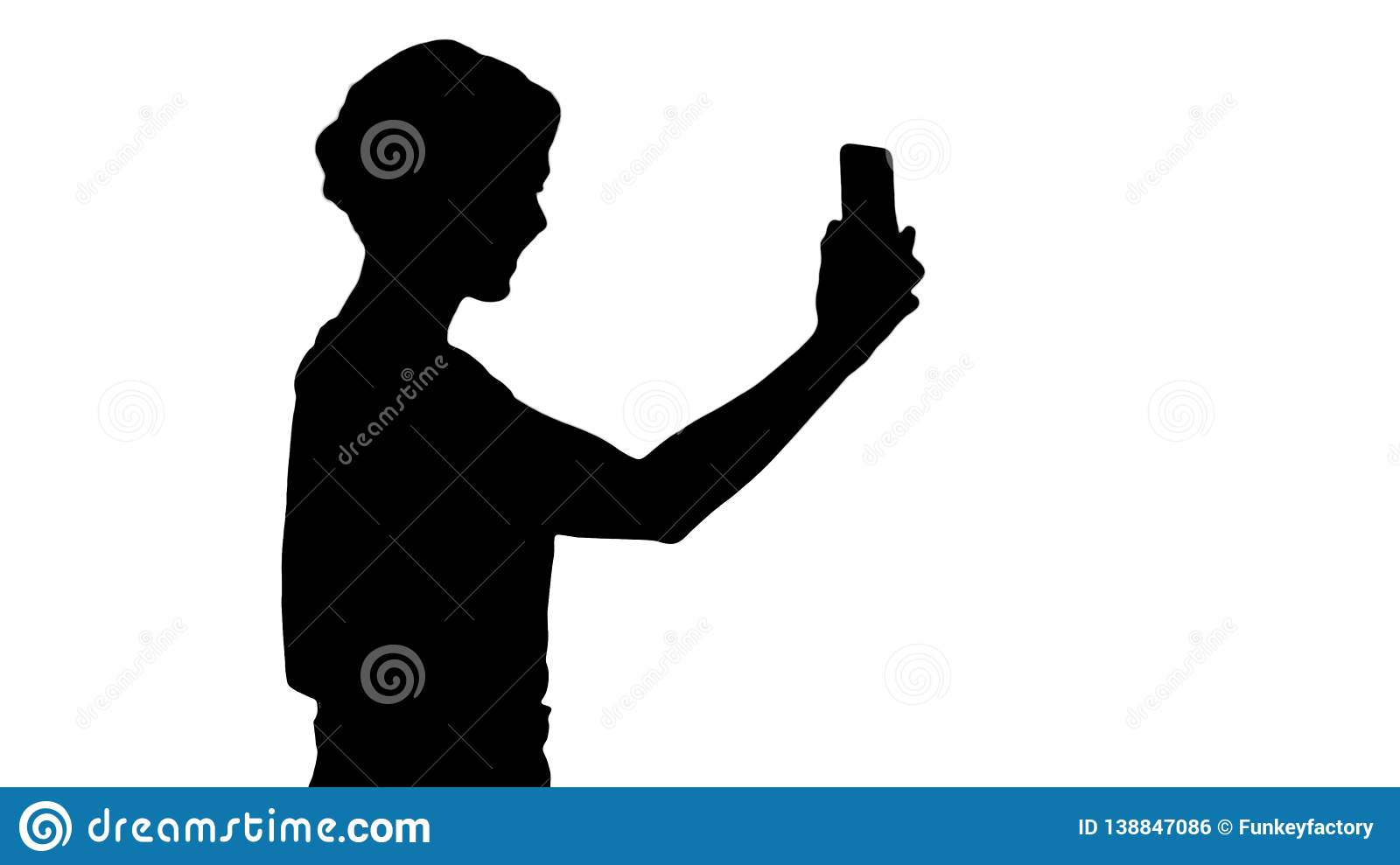 Silhouette Beautiful young woman walking and holding a smartphone up to take pictures and selfies.