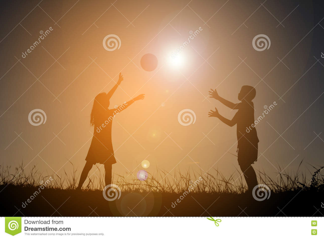Silhouette children playing football on the sky sunset. Time on