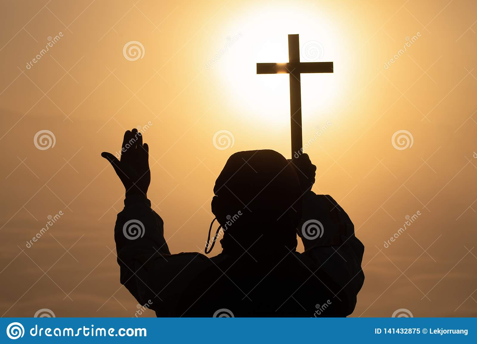 Silhouette of christian Man holding a cross, cross in hands praying for blessing from god on sunlight background, hope concept