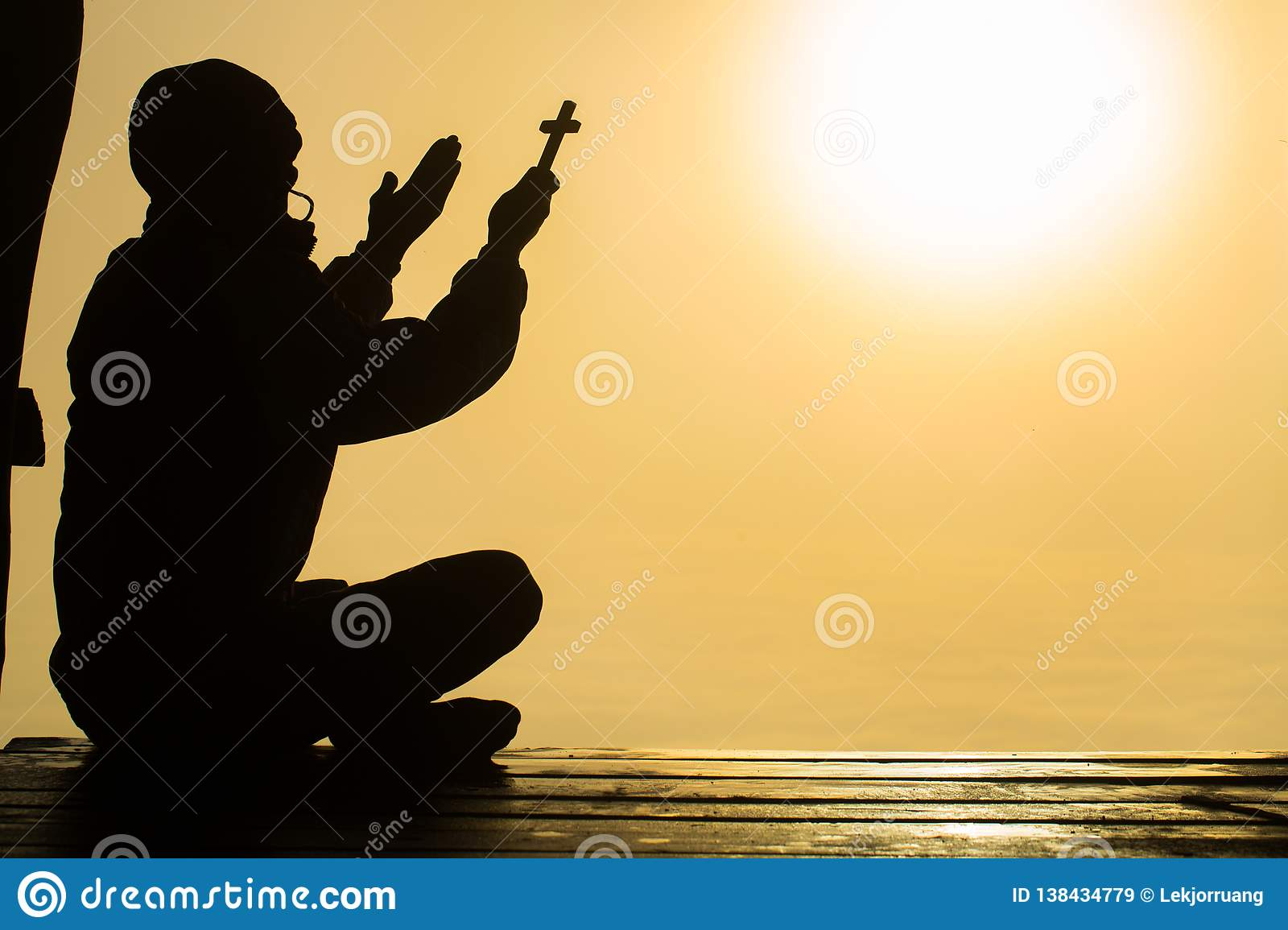 Silhouette of christian young man praying with a cross at sunrise, Christian Religion concept background