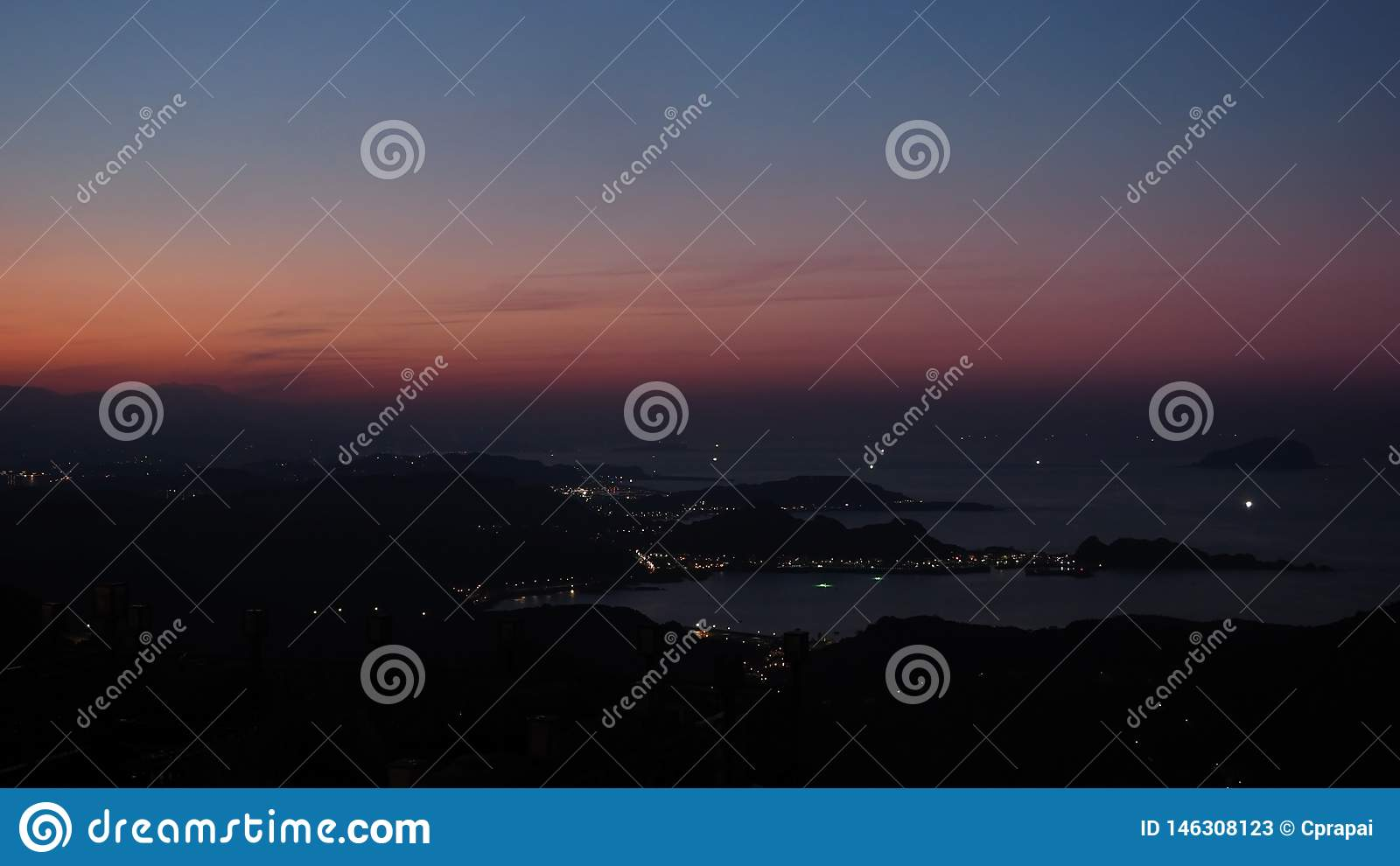 Silhouette of cityscape and mountain range with evening orange purple sunset sky. Also some city lights from houses in the costal