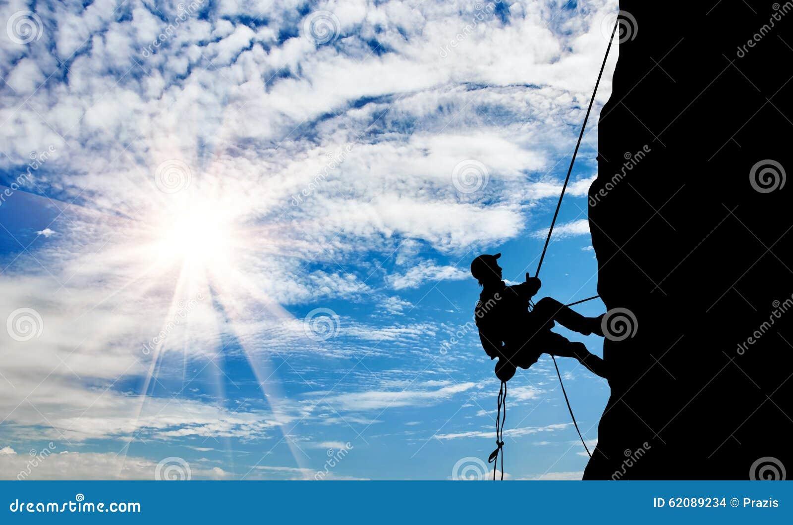 Silhouette climber climbing a mountain