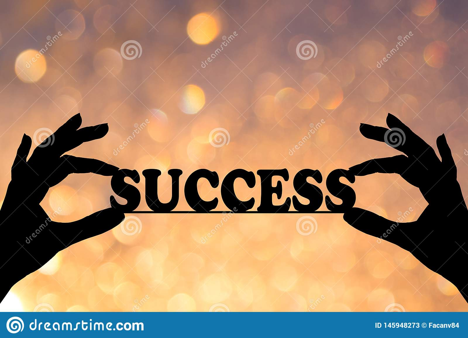 Silhouette, the conceptual text of the message `SUCCESS` in safe hands. Yellow and orange bokeh in the background.