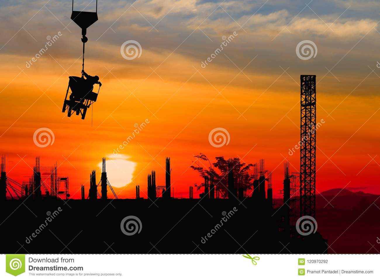 Silhouette construction worker on crane hook on sunset-sunrise time background and copy space