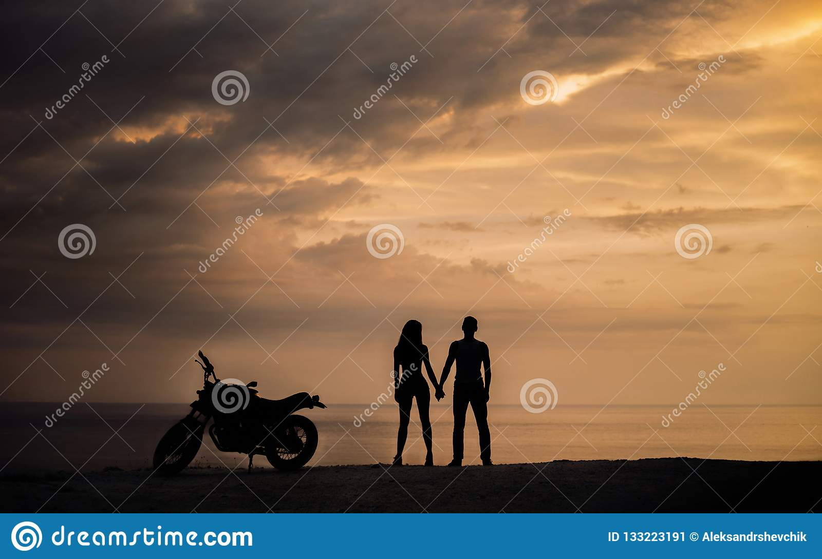 Silhouette of Couple standing with a motorbike in the sunset