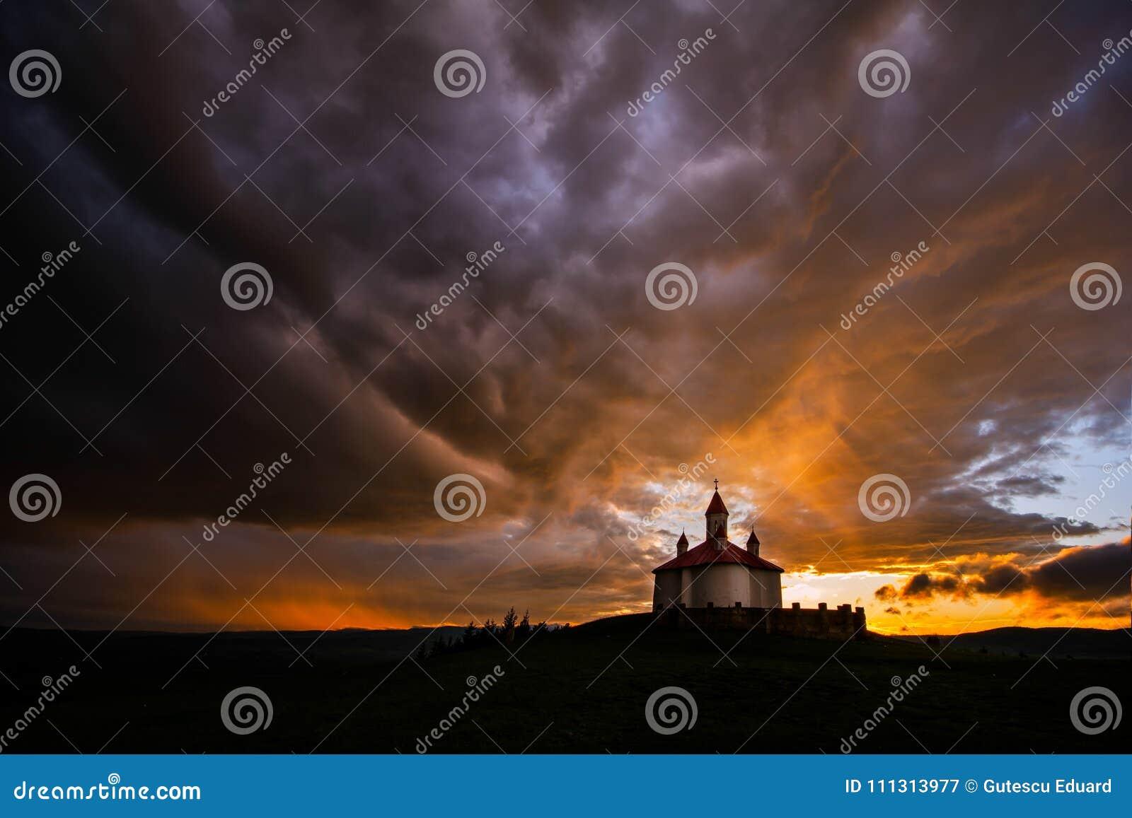 Silhouette d église roumaine avec la lumière de rayon après tempête