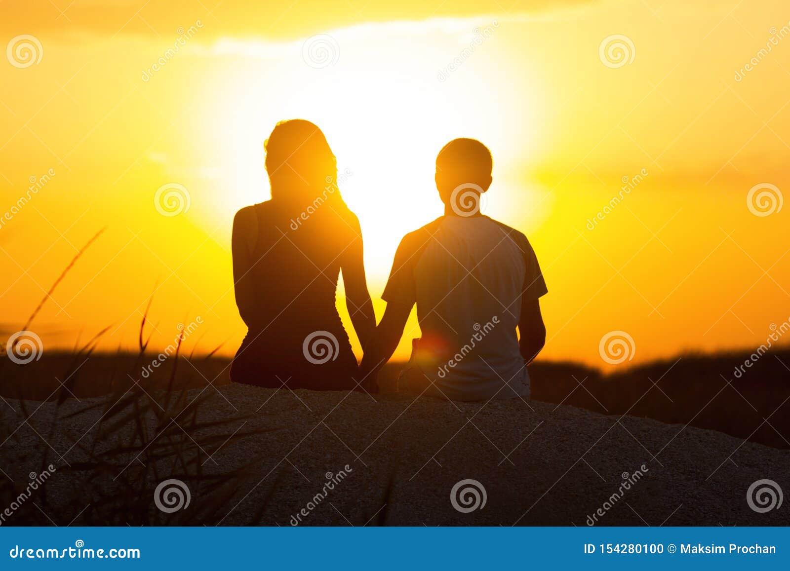 Silhouette d un couple affectueux au coucher du soleil se reposant sur le sable sur la plage, la figure d un homme et une femme d