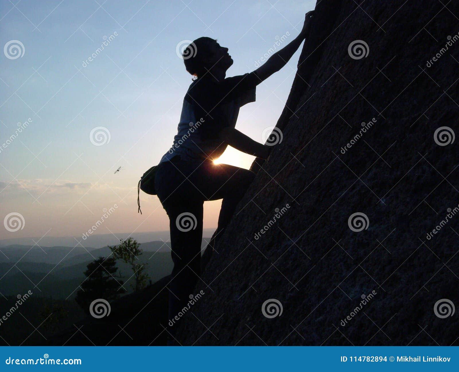 Silhouette d un jeune grimpeur masculin s élevant jusqu au dessus de la falaise au coucher du soleil sans assurance