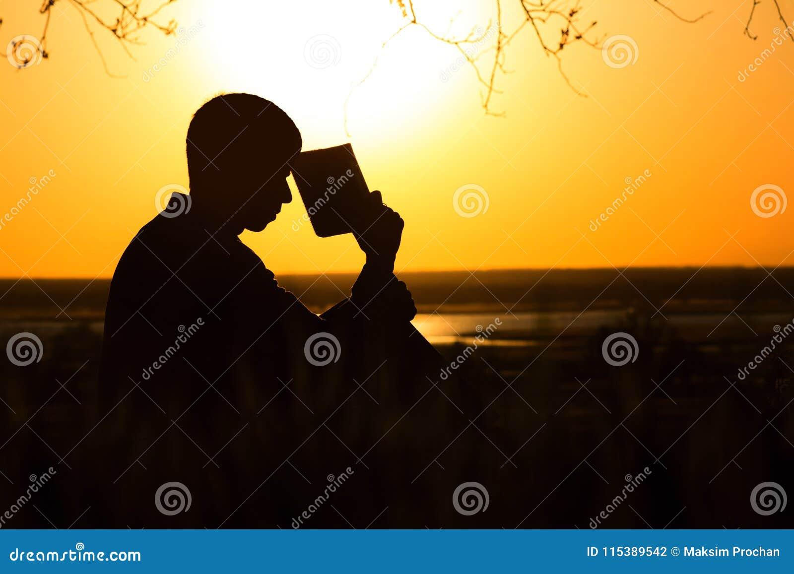 Silhouette d un jeune homme avec une bible, le mâle priant à Dieu en nature, le concept de la religion et la spiritualité