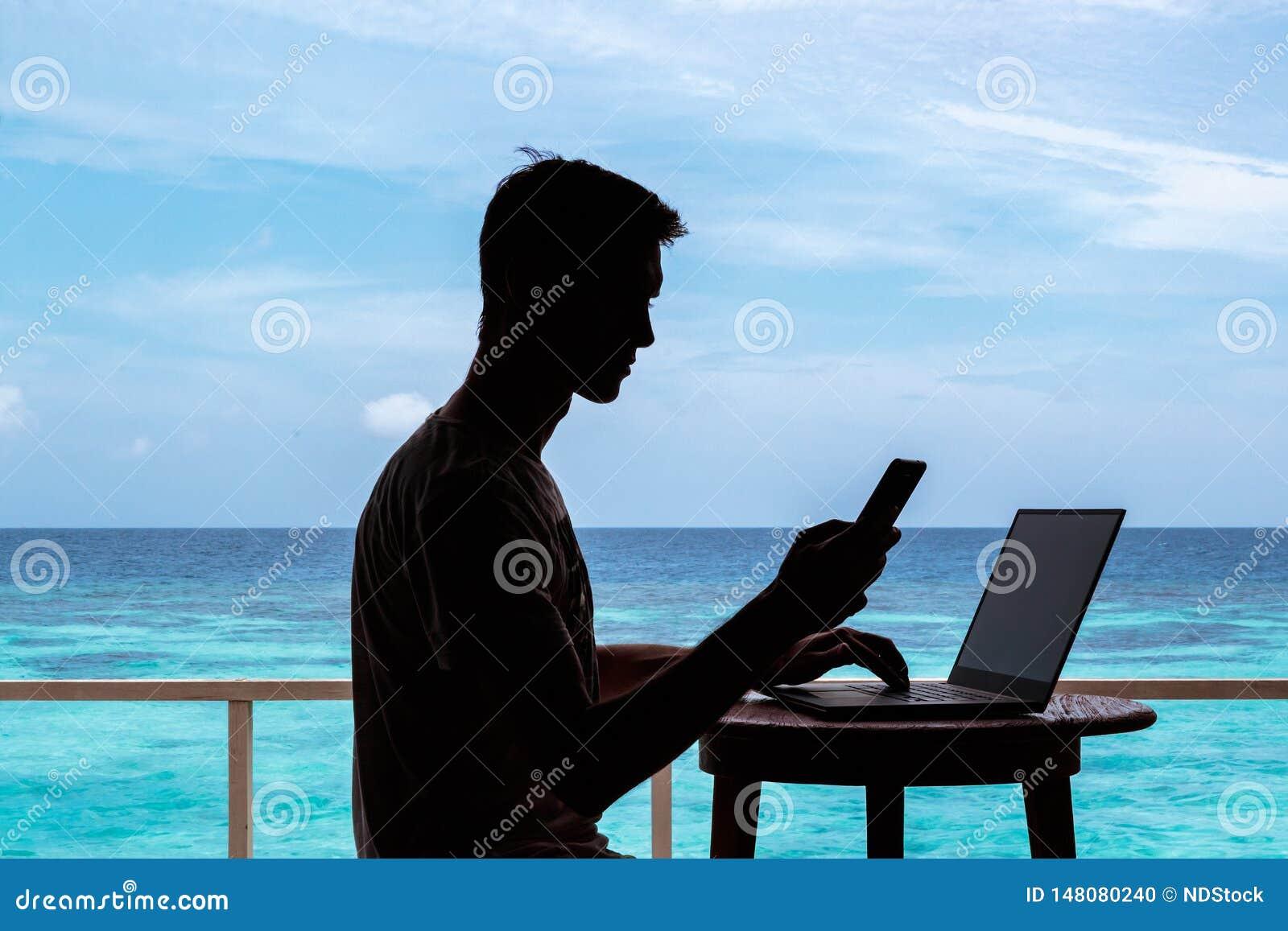 Silhouette d un jeune homme travaillant avec un ordinateur et un smartphone sur une table L eau tropicale bleue claire comme fond