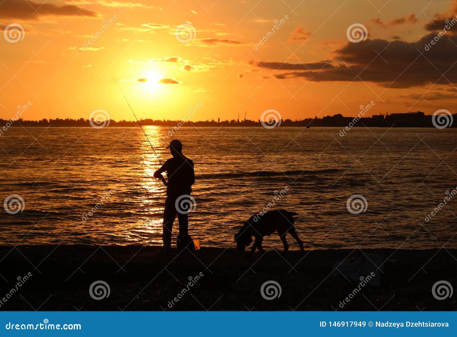 Silhouette d un pêcheur avec une canne à pêche et un chien