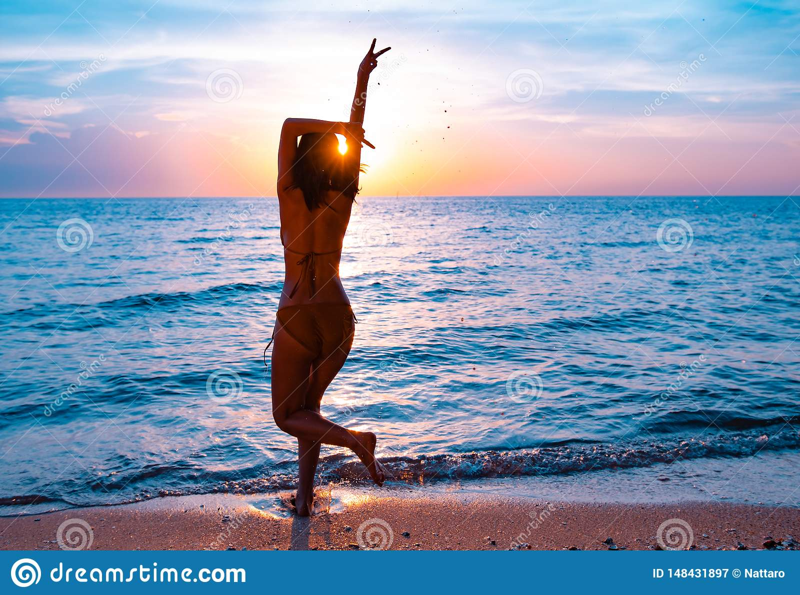 Silhouette d une belle, mince fille qui saute sur un fond d un coucher du soleil