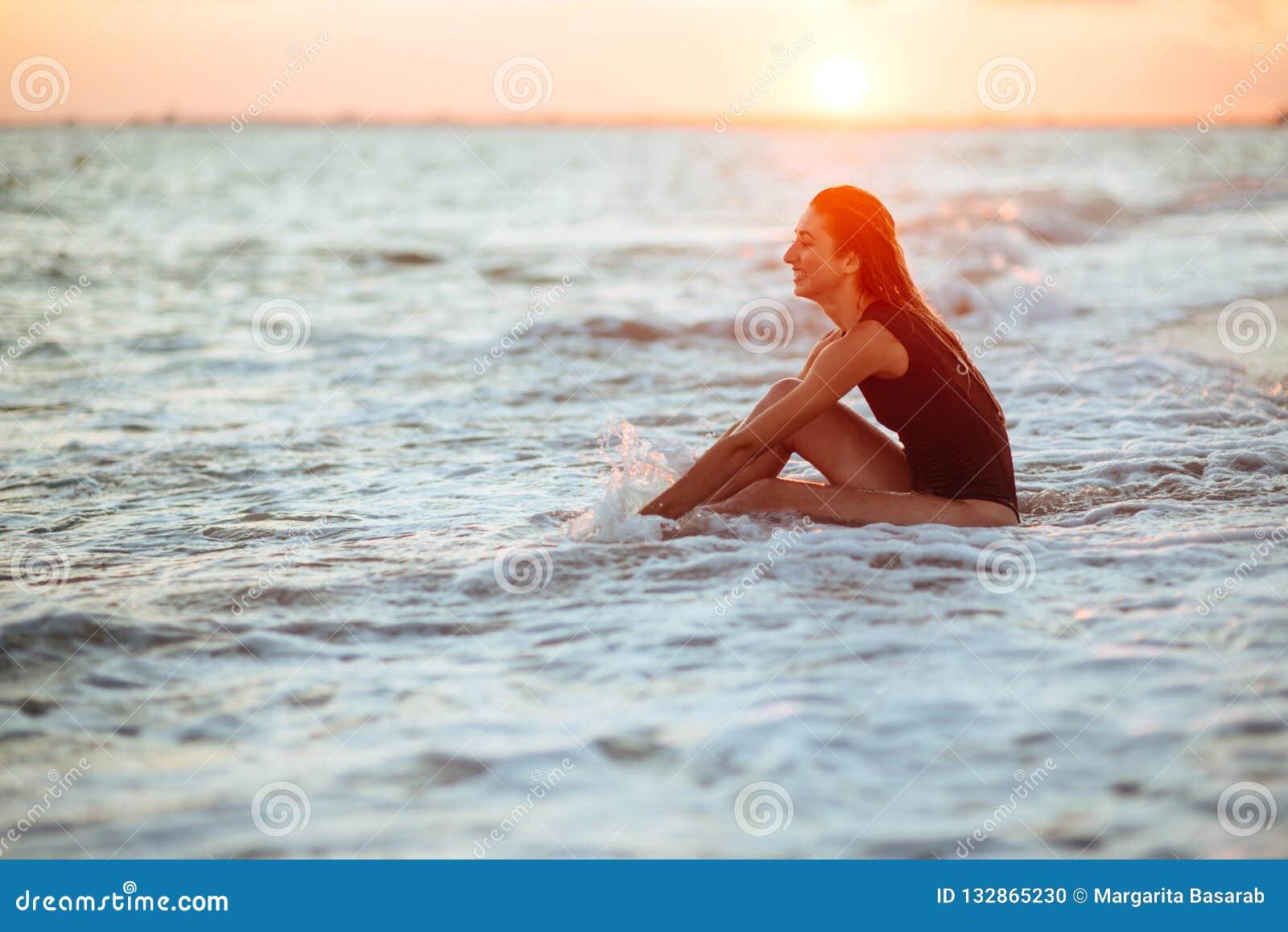 Silhouette d une fille dans l eau au coucher du soleil