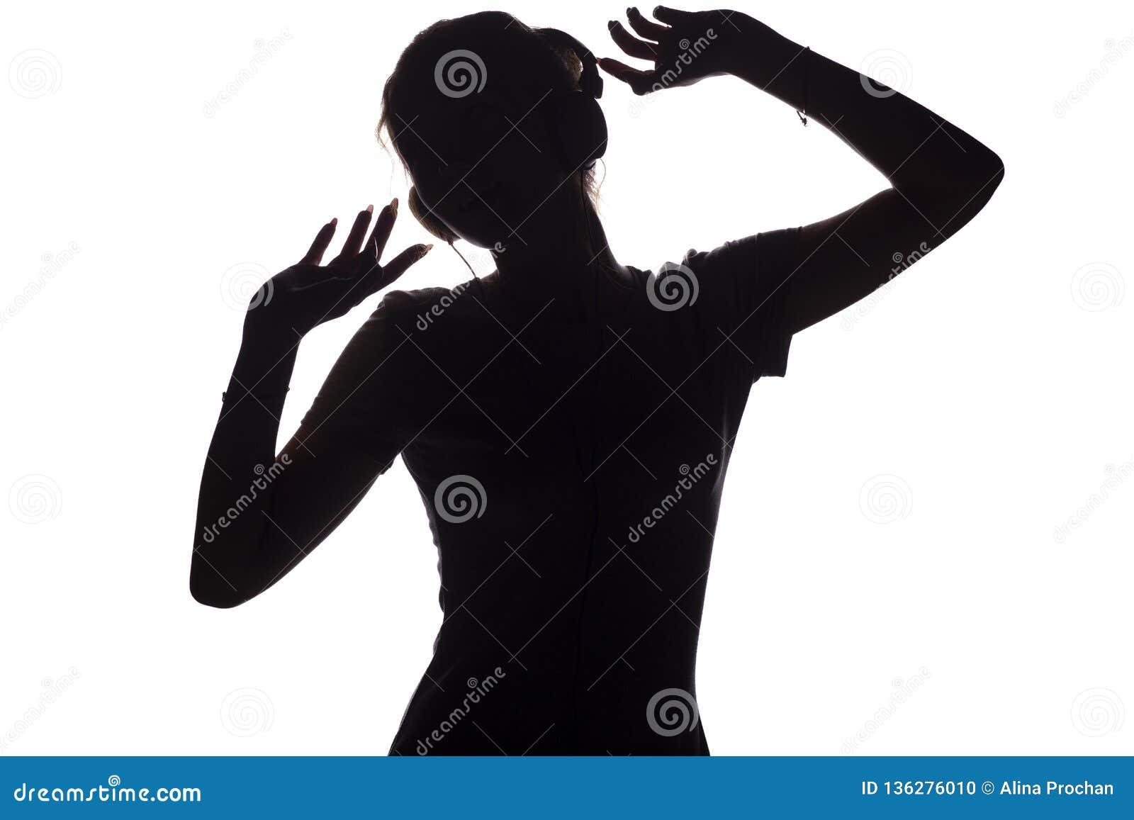 Silhouette d une fille heureuse écoutant la musique dans des écouteurs, figure de jeune femme avec des mains vers le haut de la d