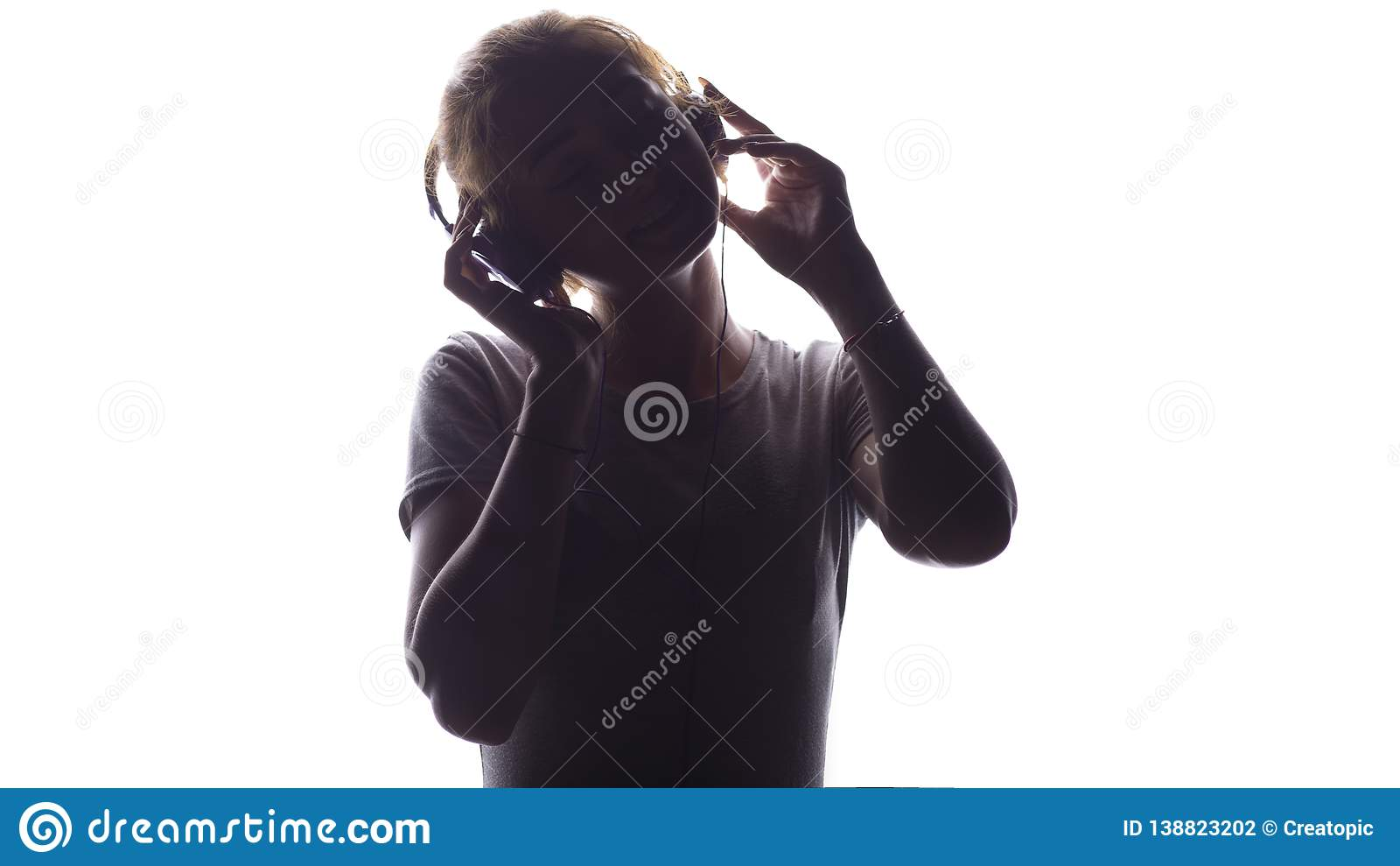 Silhouette d une fille romantique écoutant la musique dans des écouteurs, jeune femme détendant sur un fond blanc, concept de