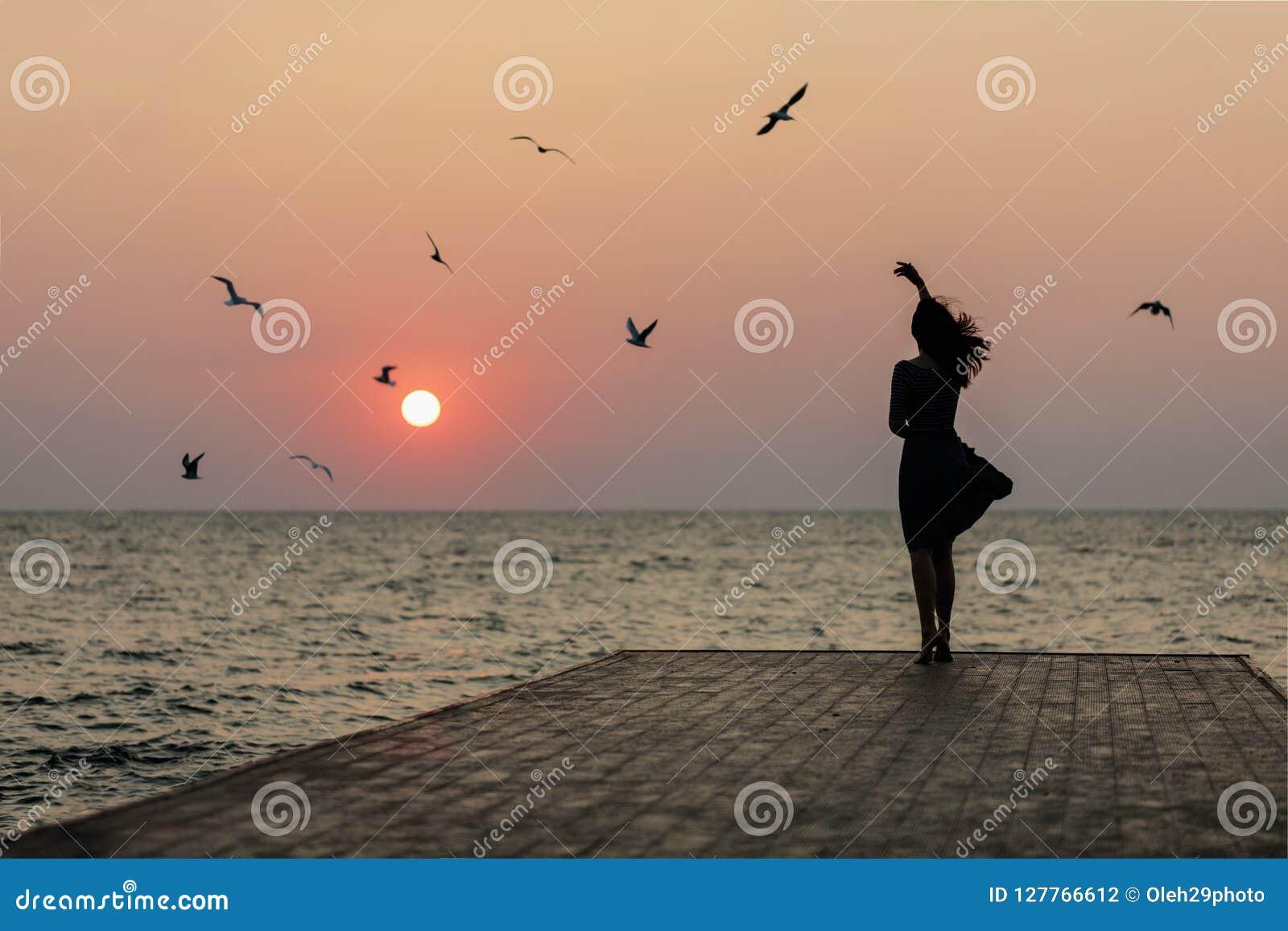 Silhouette d une fille sur un lever de soleil de fond de coucher du soleil sur la mer