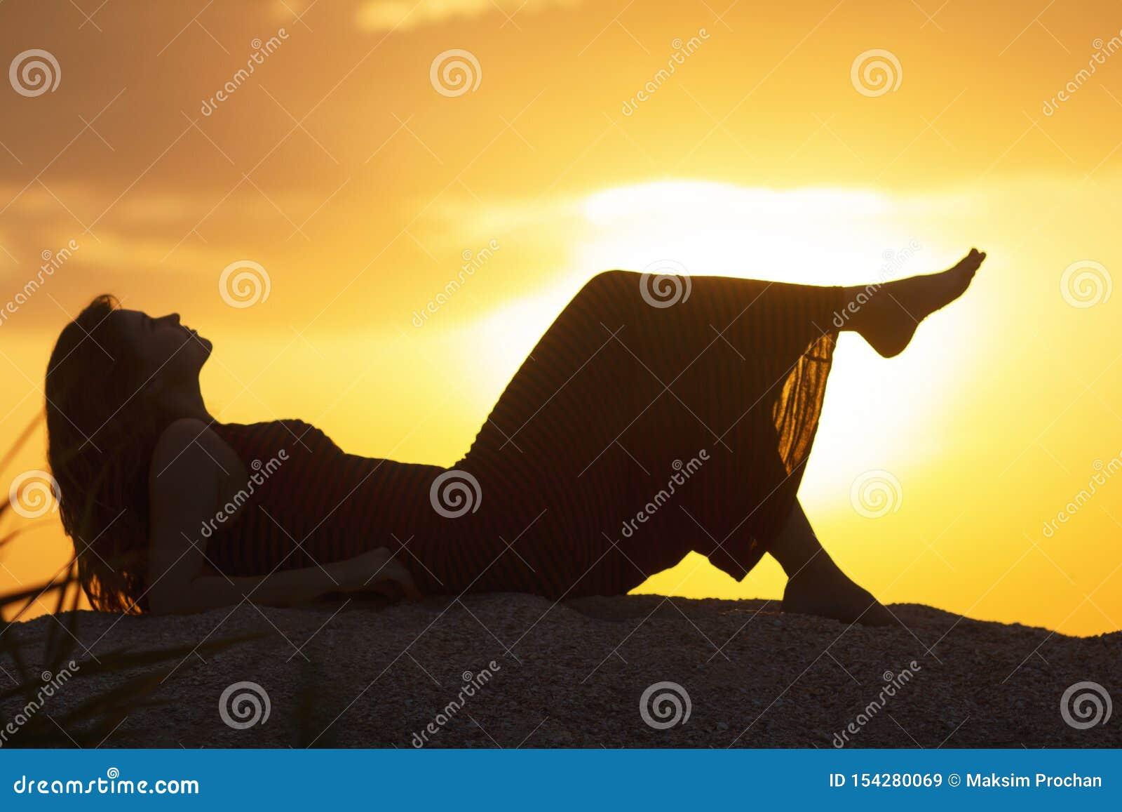 Silhouette d une jeune belle fille se situant dans une robe sur le sable et appréciant le coucher du soleil, la figure d une femm