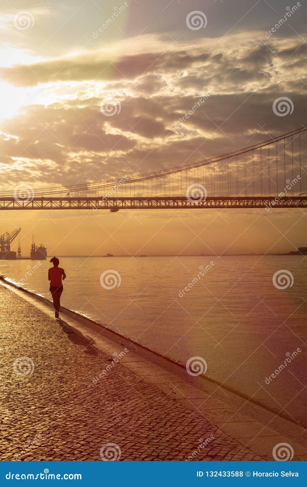 Silhouette d une jeune femme courant en bas du pilier Un pont énorme du trafic