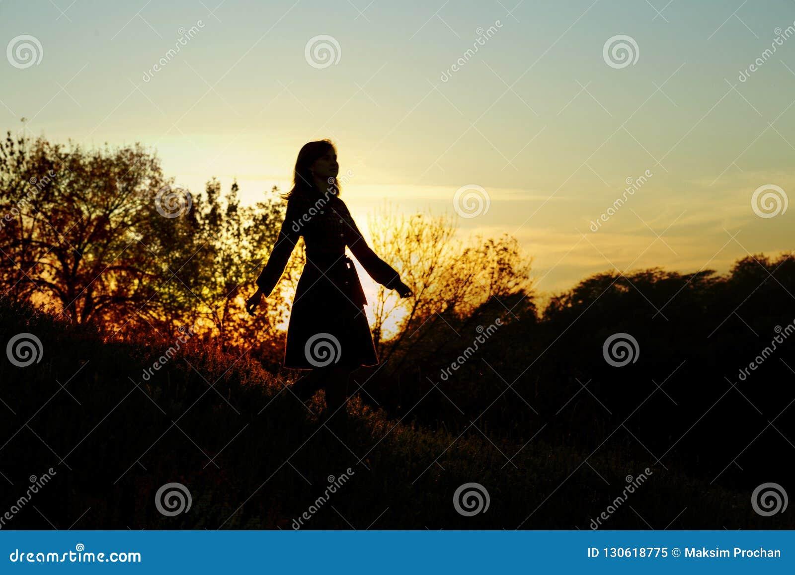 Silhouette d une jeune femme descendant d une colline au coucher du soleil, une fille marchant pendant l automne dans le domaine