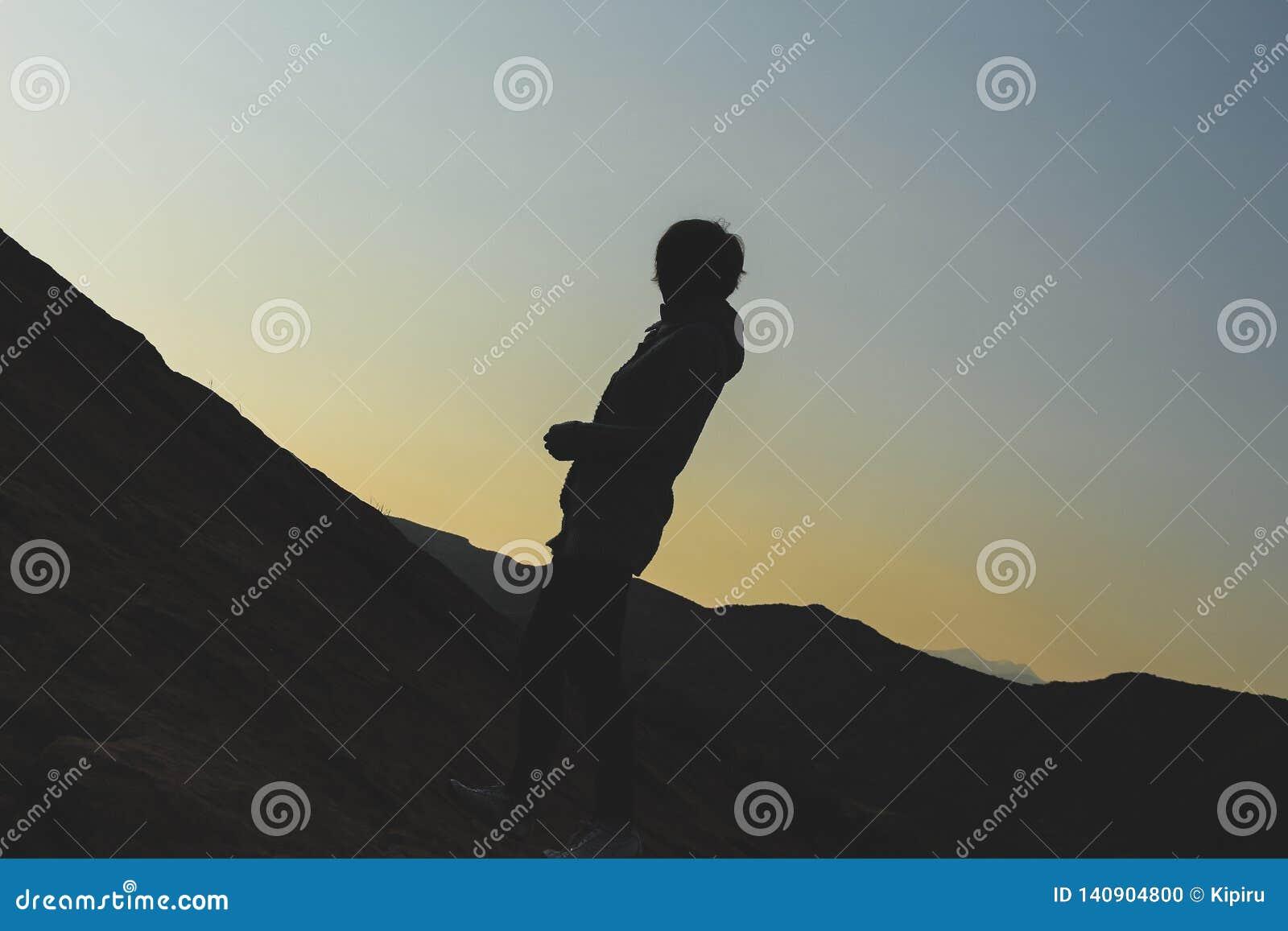 Silhouette d une jeune femme trimardant sur la colline