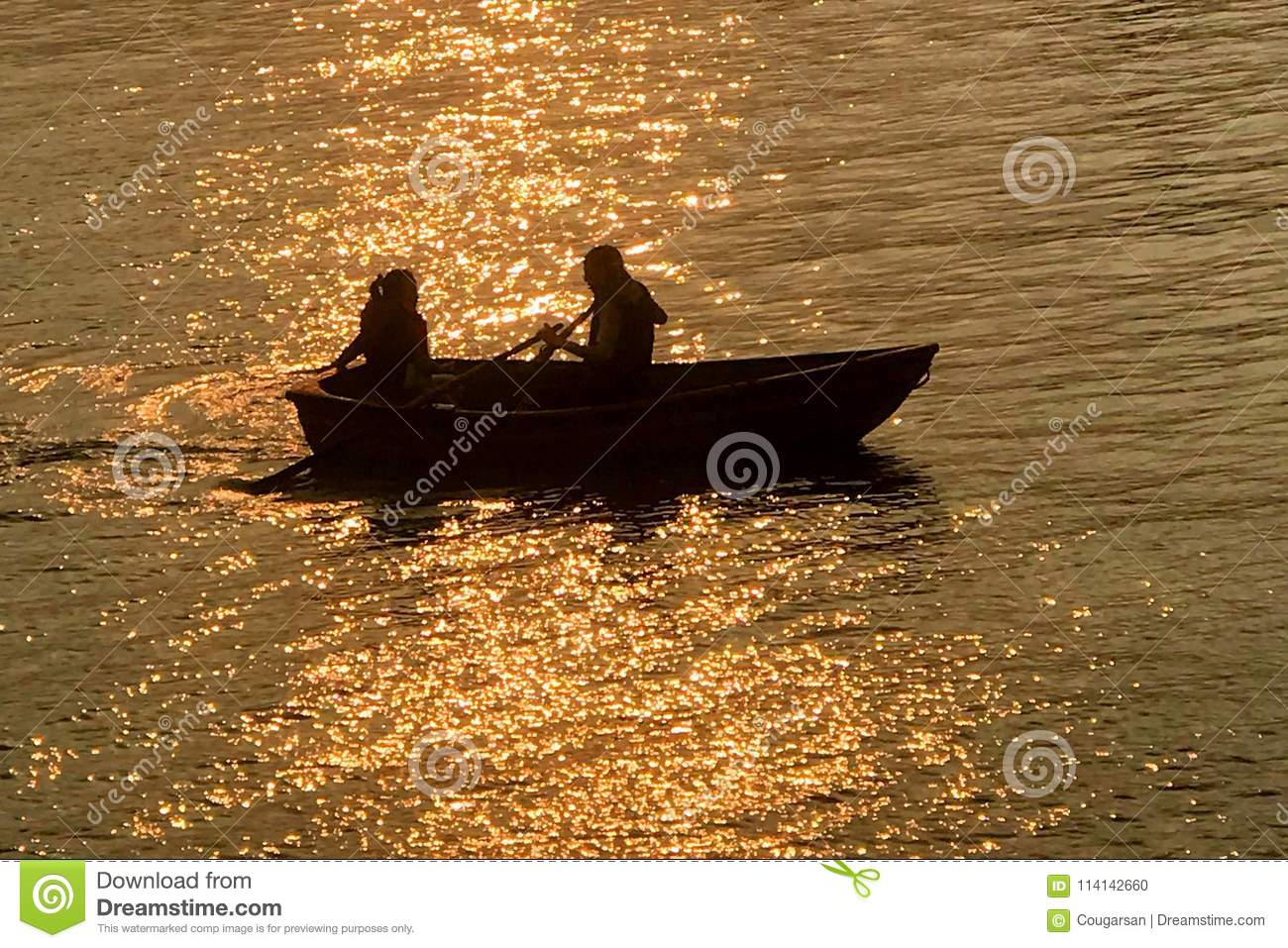 Silhouette of dating couple, recreational boat on lake at sunset