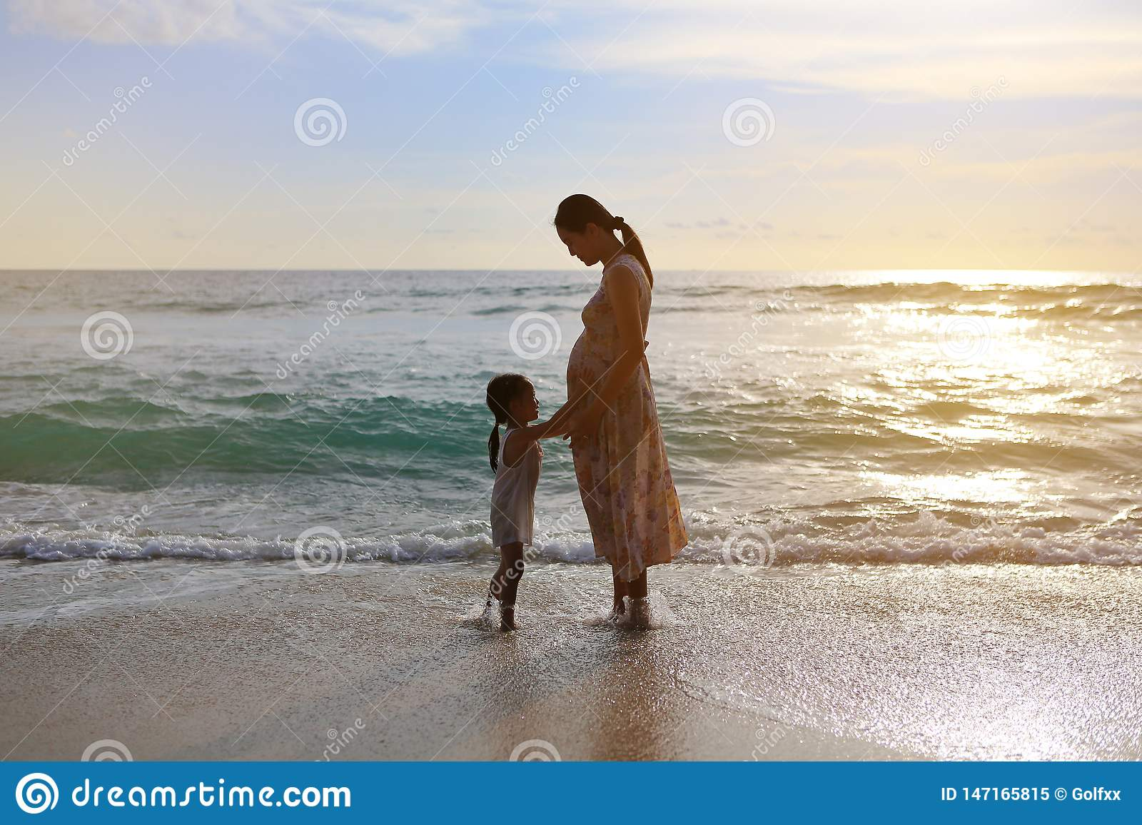 Silhouette daughter touching belly of pregnant mother and relaxing on the beach at sunset