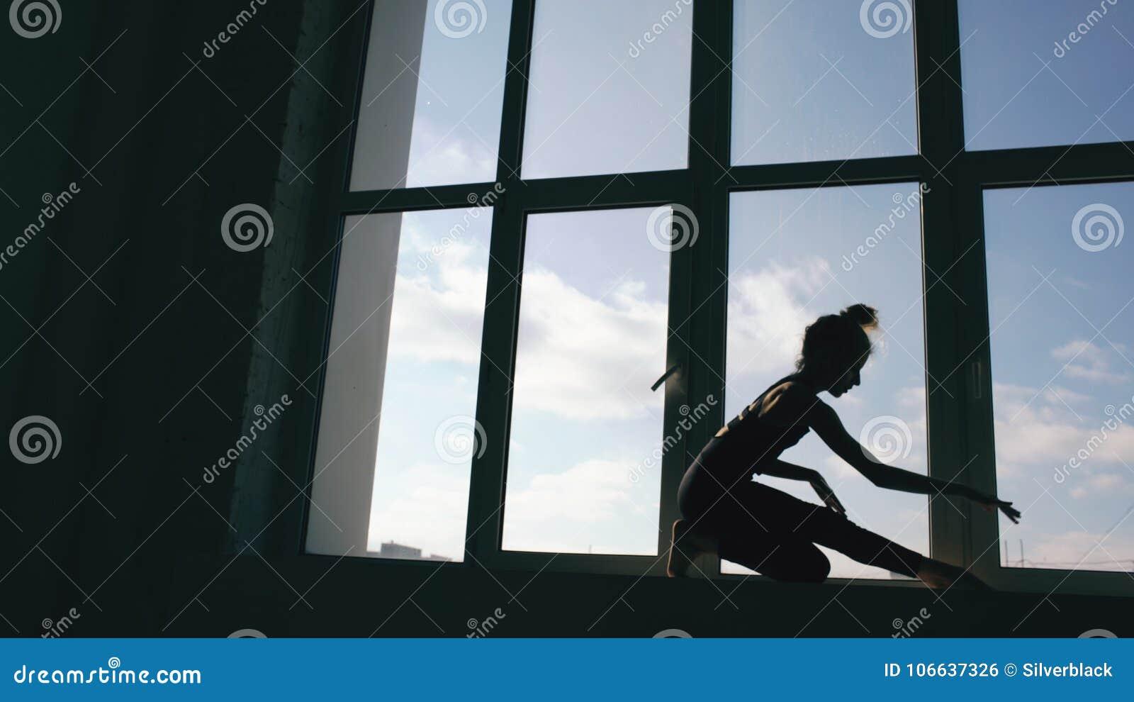 Silhouette de danse contemporaine de représentation de danseuse de jeune fille sur le windowsiil dans le studio de danse à l inté