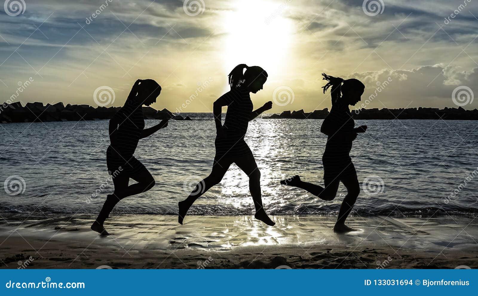 Silhouette de femme de coureur, fonctionnant sur la plage au coucher du soleil