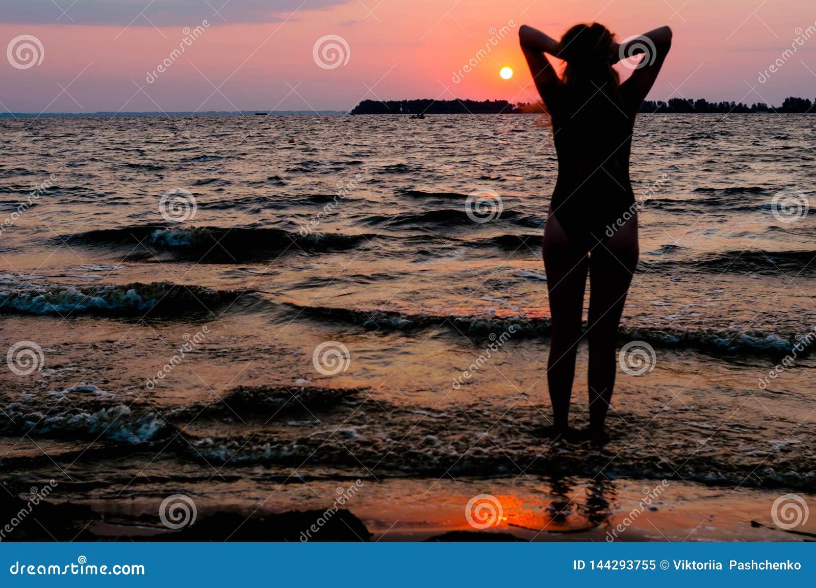 Silhouette de femme dans le maillot de bain avec les bras augmentés regardant le lever de soleil stupéfiant près de la mer