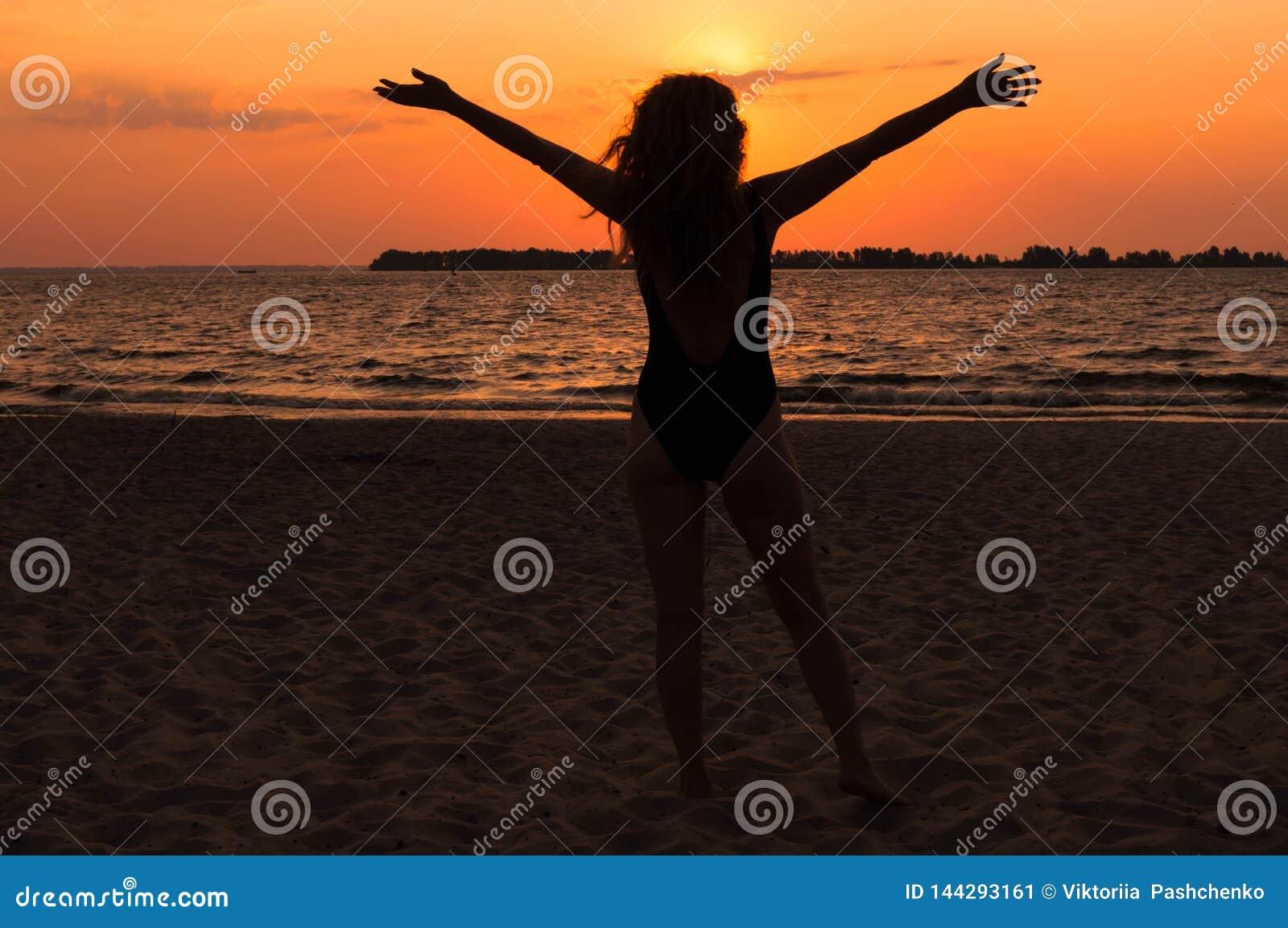 Silhouette de femme dans le maillot de bain avec les cheveux débordants, les mains augmentées et la position sur la plage près de