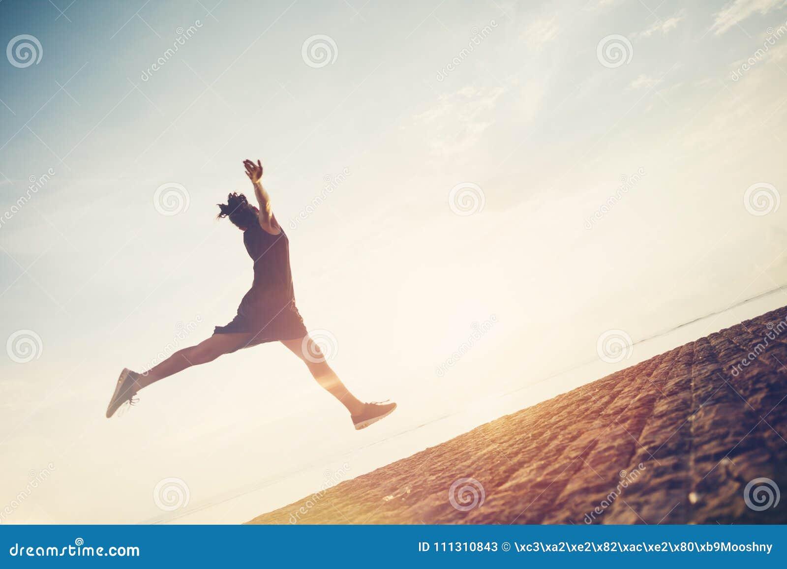 Silhouette de femme gaie sautant près de l océan Avoir le bons temps et amusement