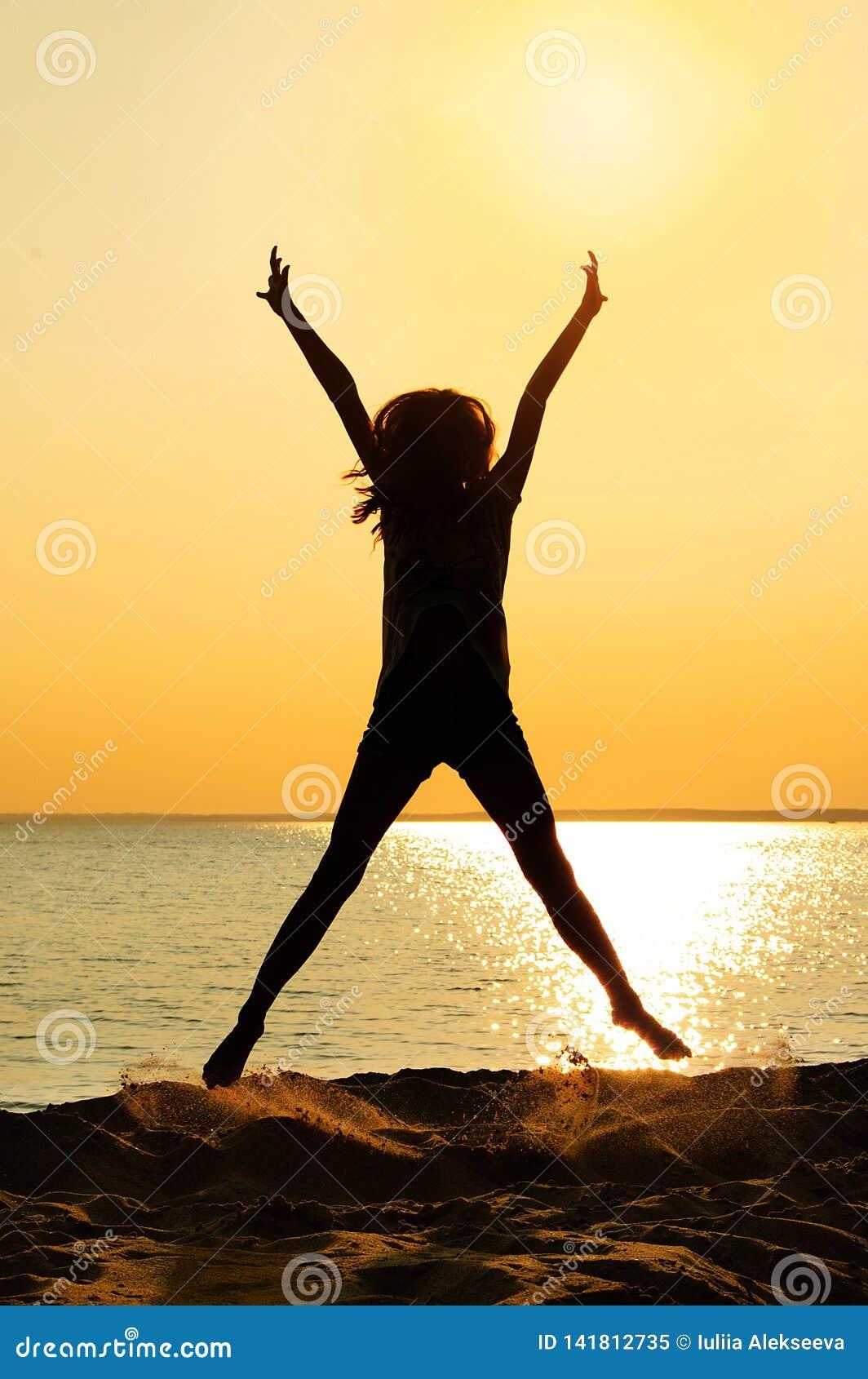 Silhouette de fille sautante Été sur la plage au coucher du soleil