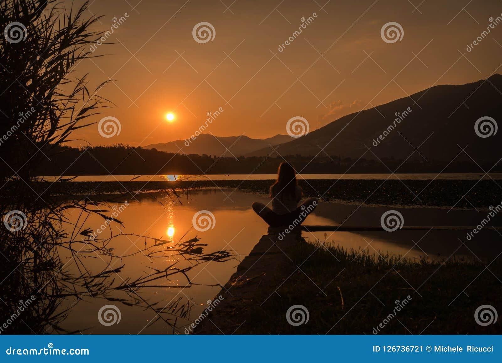 Silhouette de fille se tenant au-dessus de l amountain de lac en position de yoga de loto