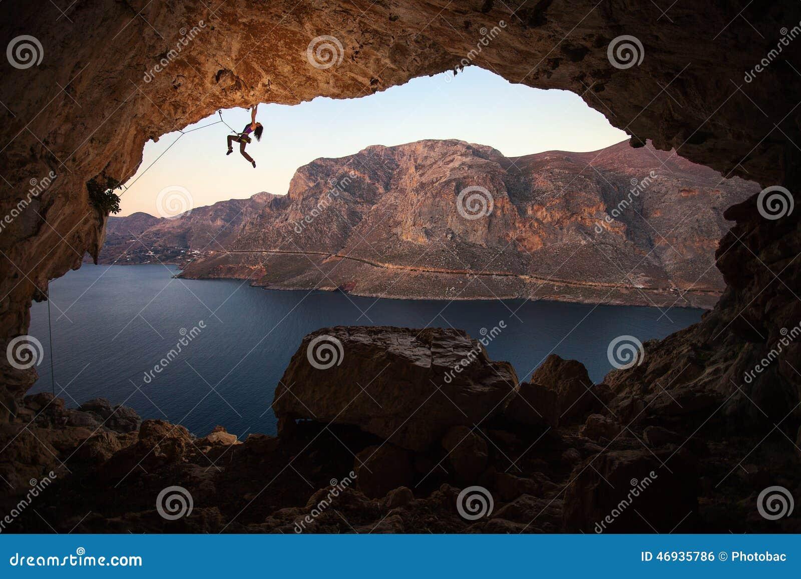 Silhouette de grimpeur de roche féminin sur la falaise en caverne