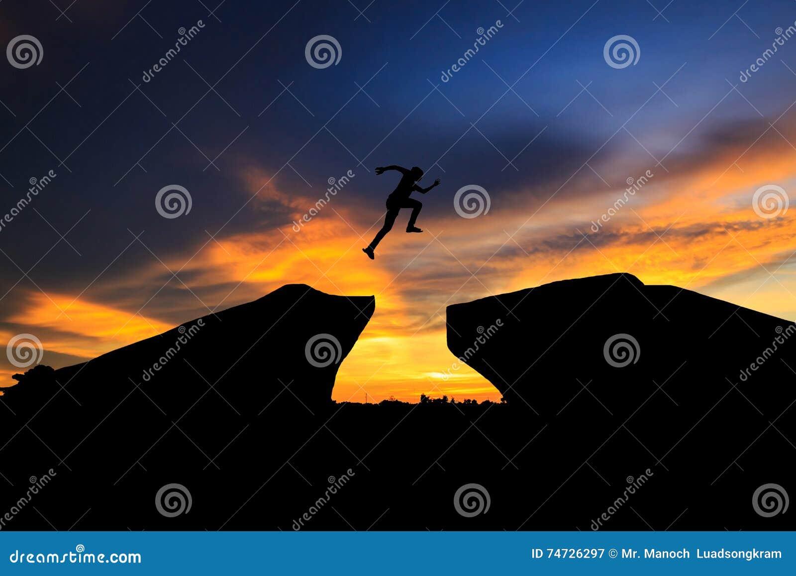 Silhouette de l homme sautant par-dessus la falaise sur le fond de coucher du soleil