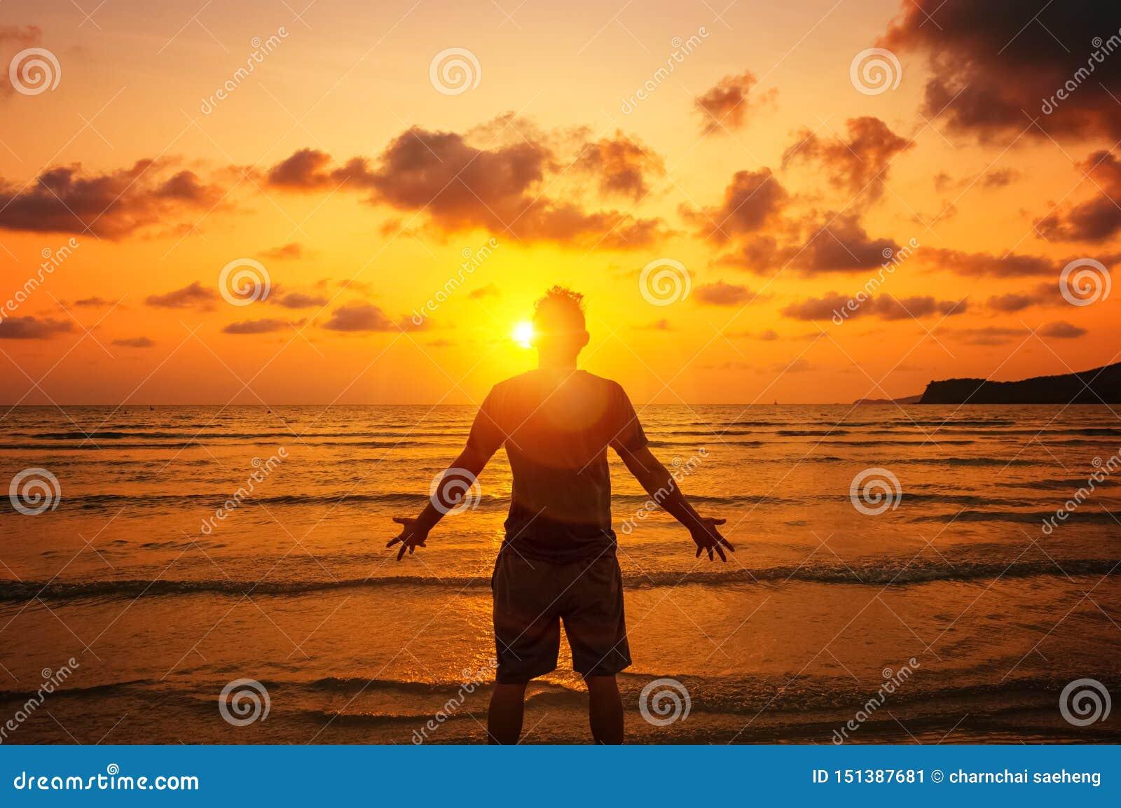 Silhouette de l homme soulevant ses mains ou bras ouverts avec le coucher du soleil