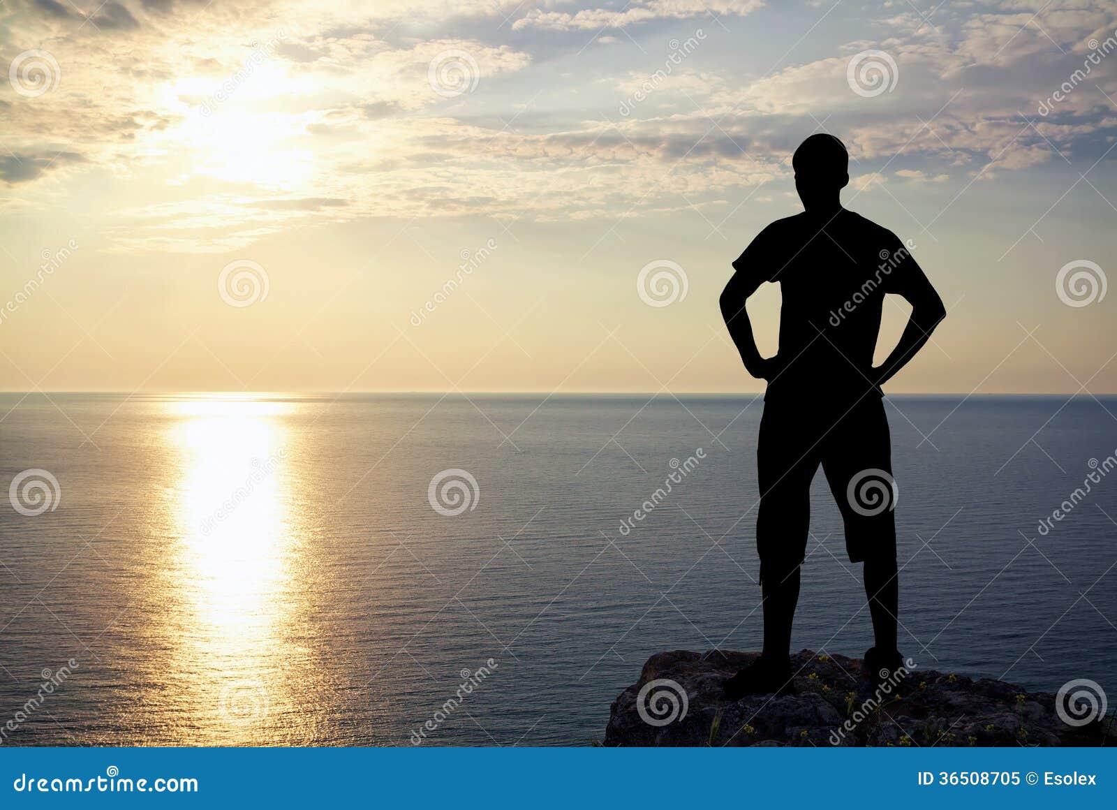Silhouette de l homme sur la roche au coucher du soleil.