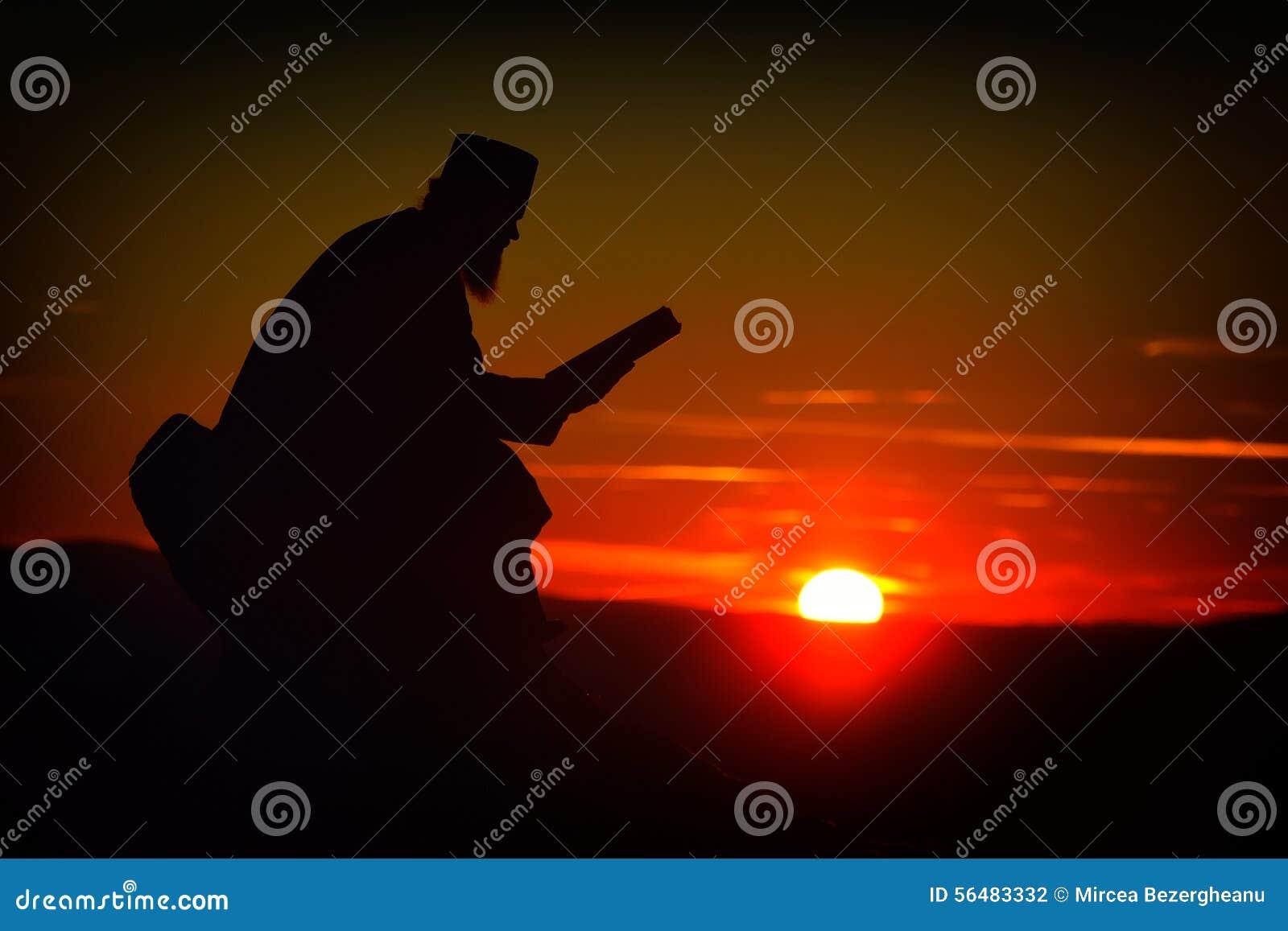 Silhouette de la lecture de prêtre dans la lumière de coucher du soleil