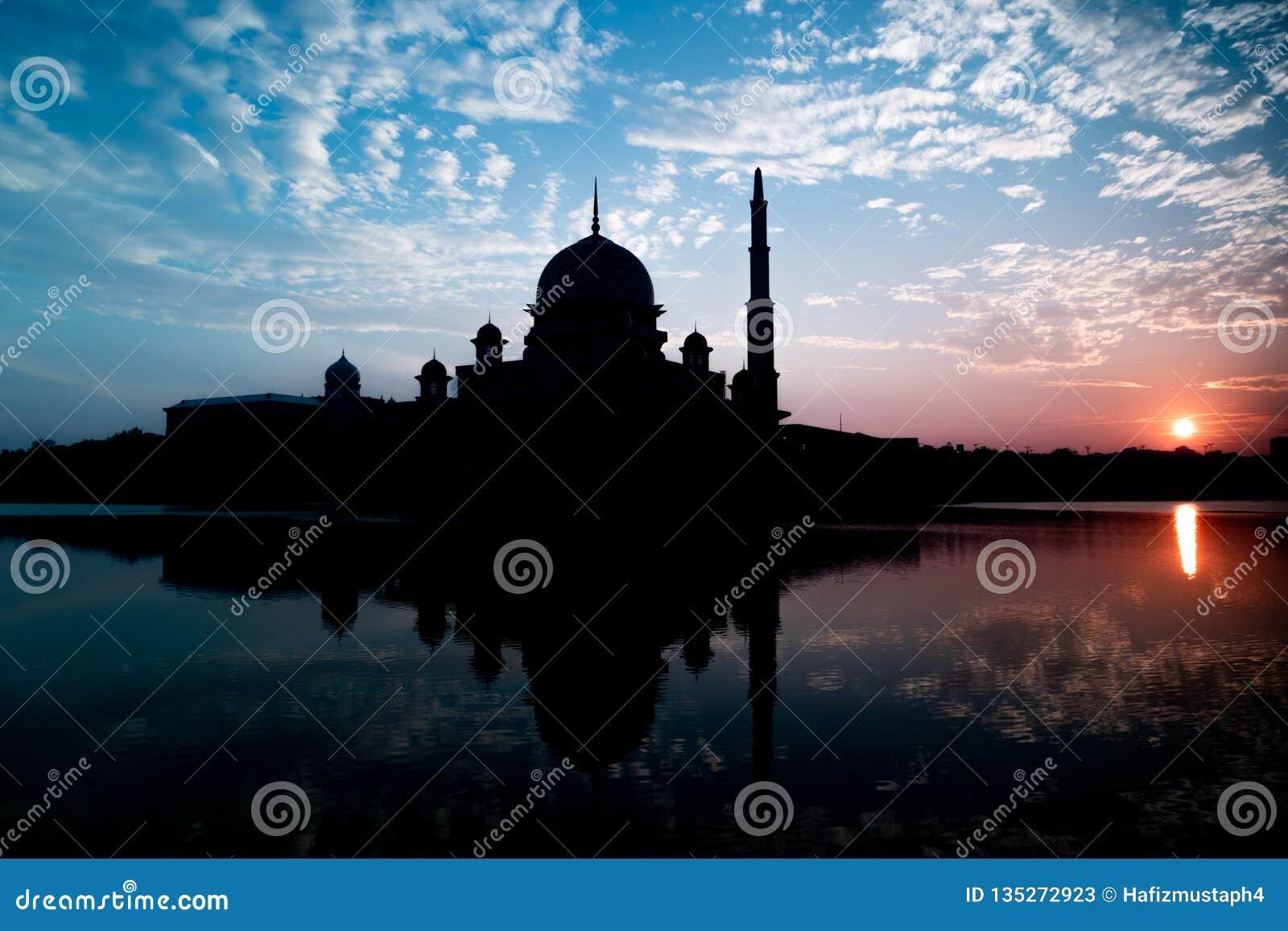 Silhouette de mosquée de Putra pendant le lever de soleil avec la réflexion dans le lac