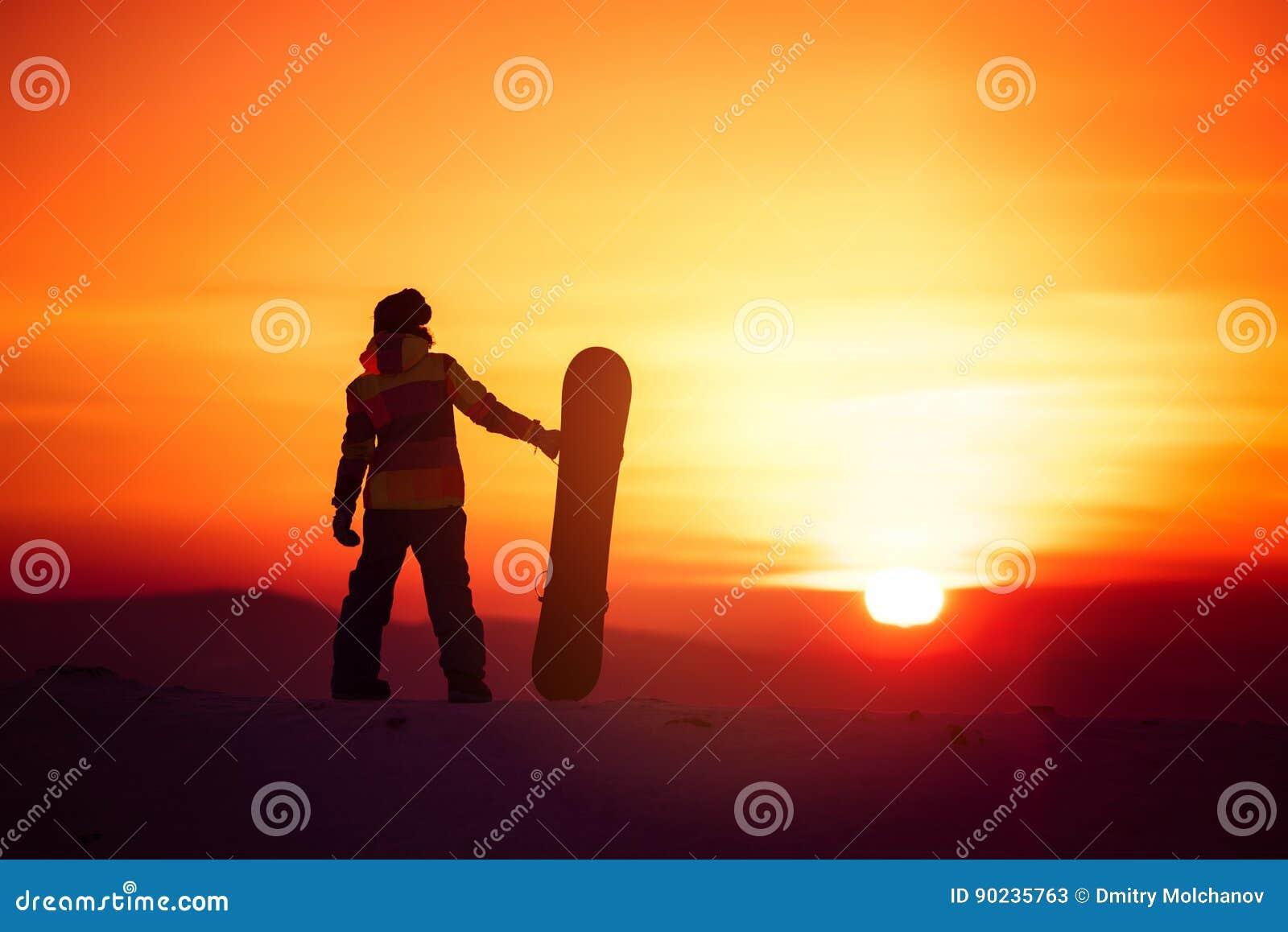 Silhouette de surfeur de femme sur le contexte de coucher du soleil