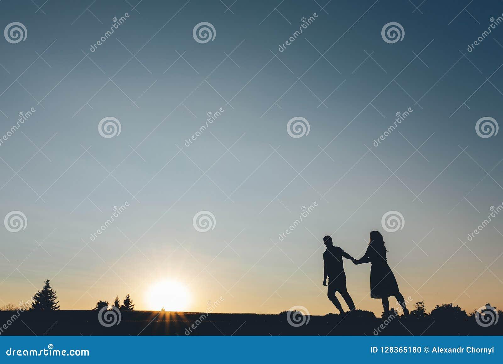 Silhouette des couples que se tenant remet des montées à la colline