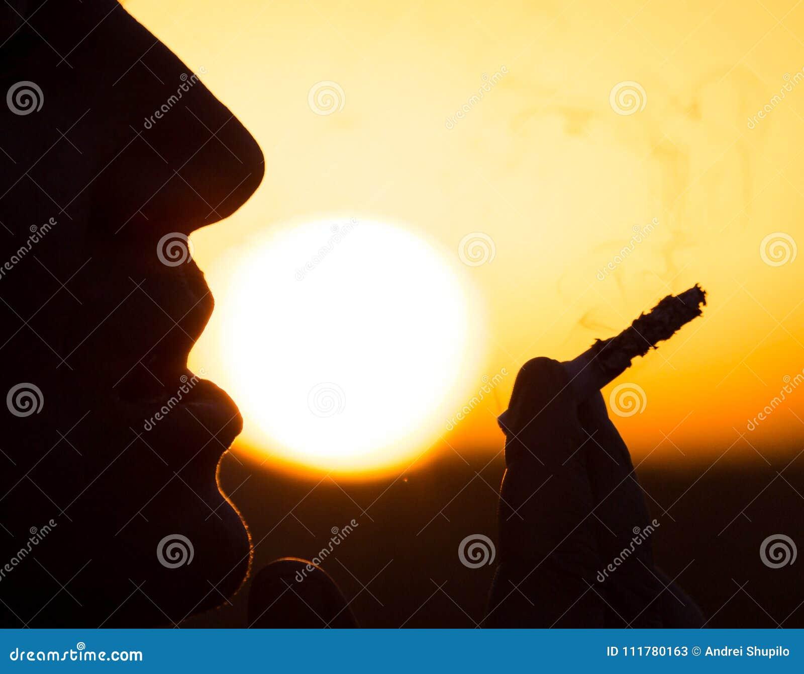 Silhouette des fumeurs masculins dans le coucher du soleil