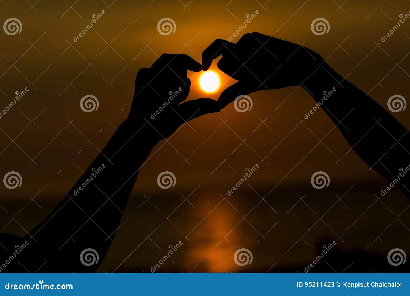 Silhouette des mains faisant un symbole en forme de coeur avec le beau fond de coucher du soleil