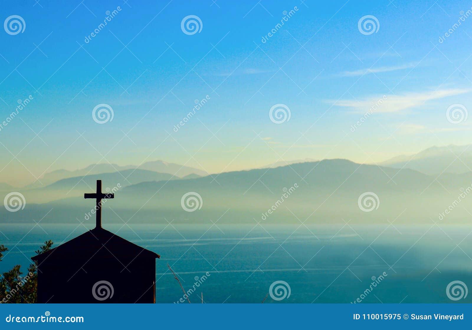 Silhouette du bâtiment avec la croix sur le dessus devant la gamme de montagne brouillée par le brouillard profond à travers le c