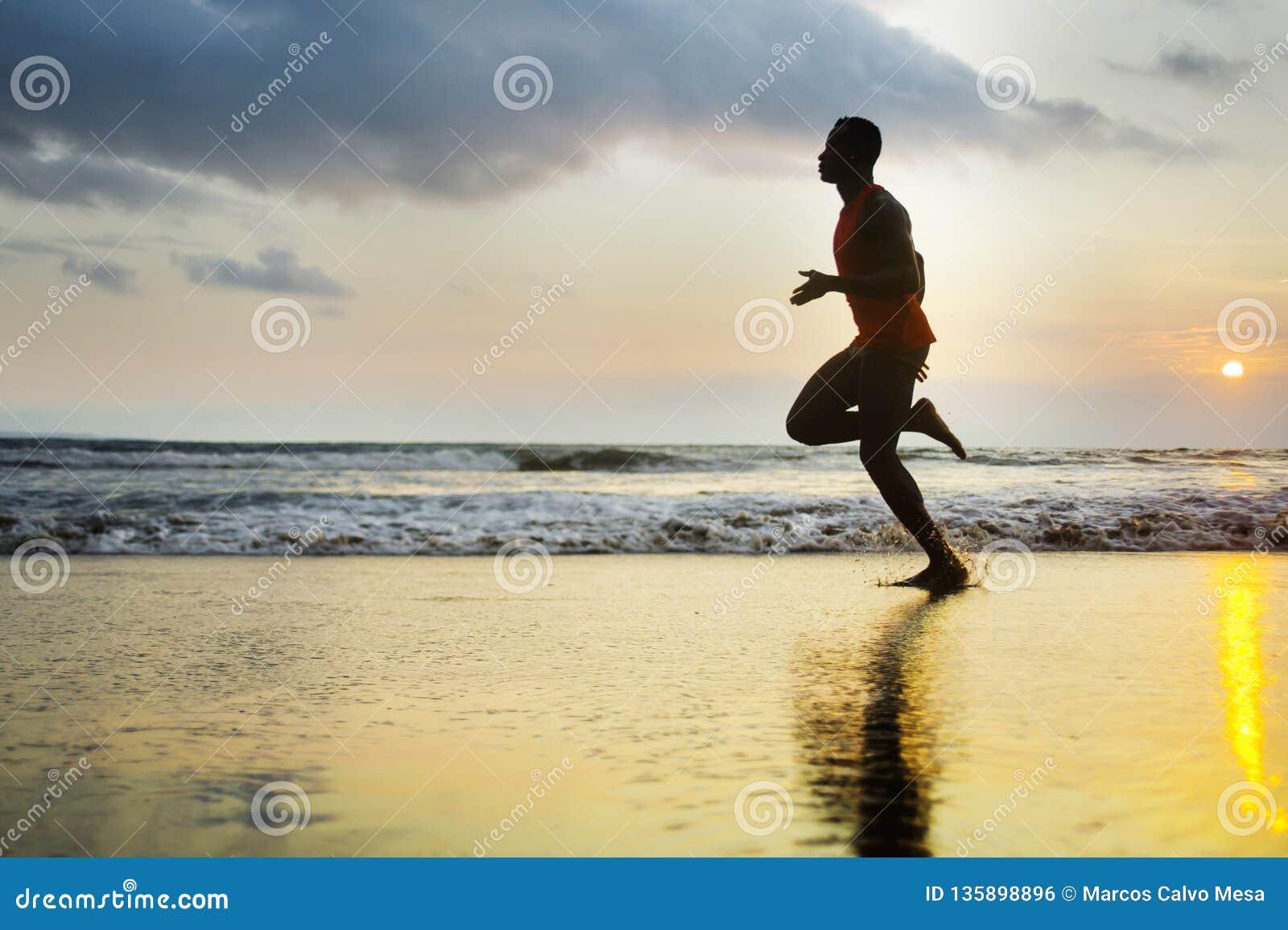 Silhouette du jeune ajustement attrayant sportif et de l homme afro-américain noir fort courant à la formation de plage de couche