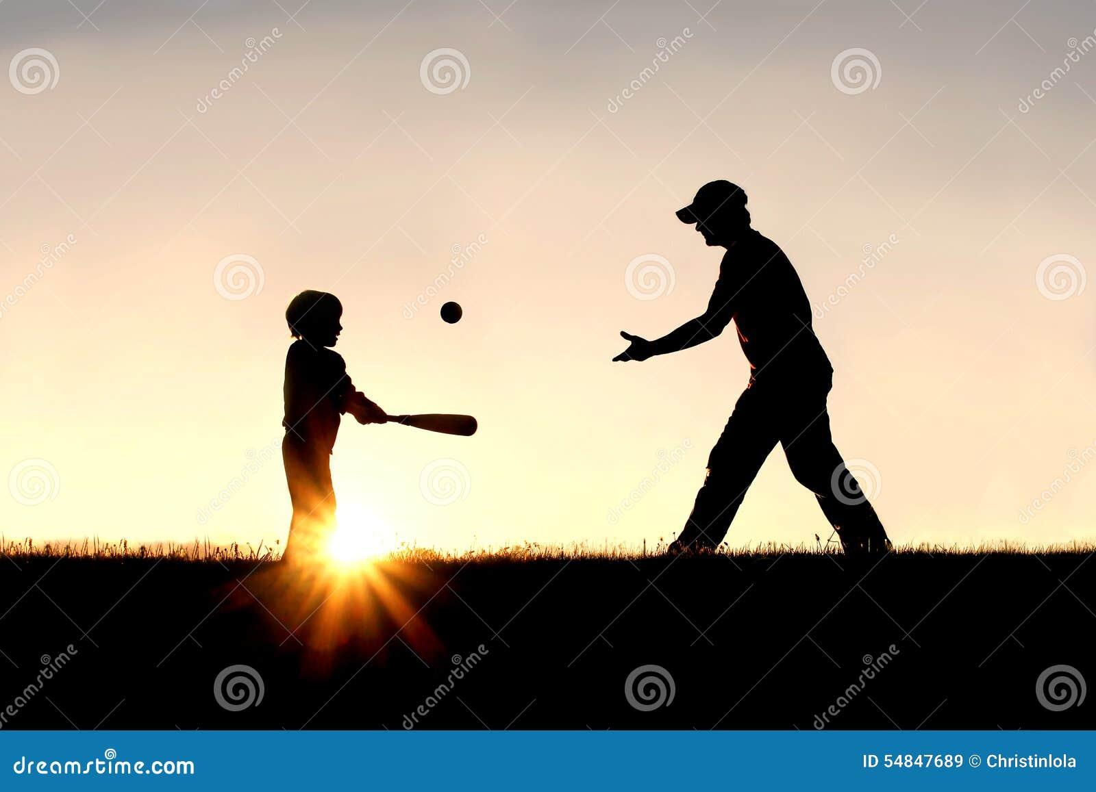 Silhouette du père et du fils jouant le base-ball dehors